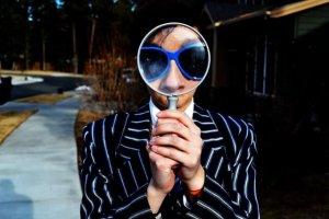 虫眼鏡をみる男性